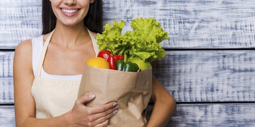 Mujer carga bolsa con hortalizas