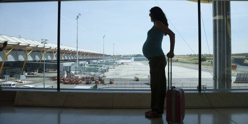 Mujer de pie junto a maleta en el aeropuerto