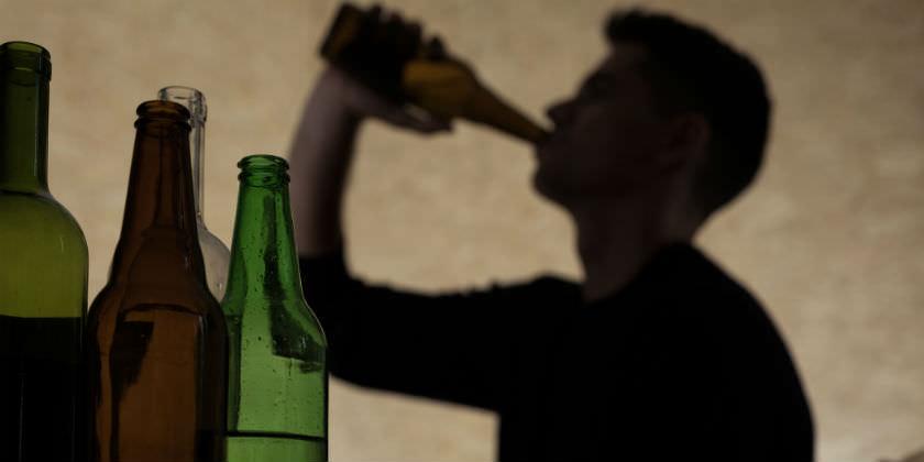 Botellas y sombra de un hombre bebiendo