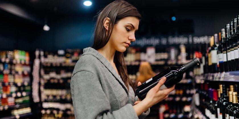Mujer mirando los ingredientes de una botella de vino.