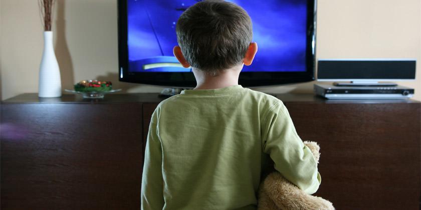 Niño mirando una televisión sólo mientras agarra un peluche.