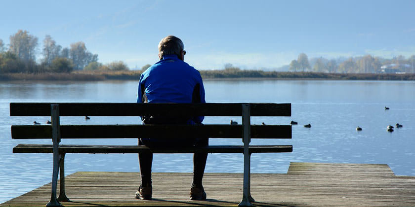 Hombre sentado en un banco delante de un lago