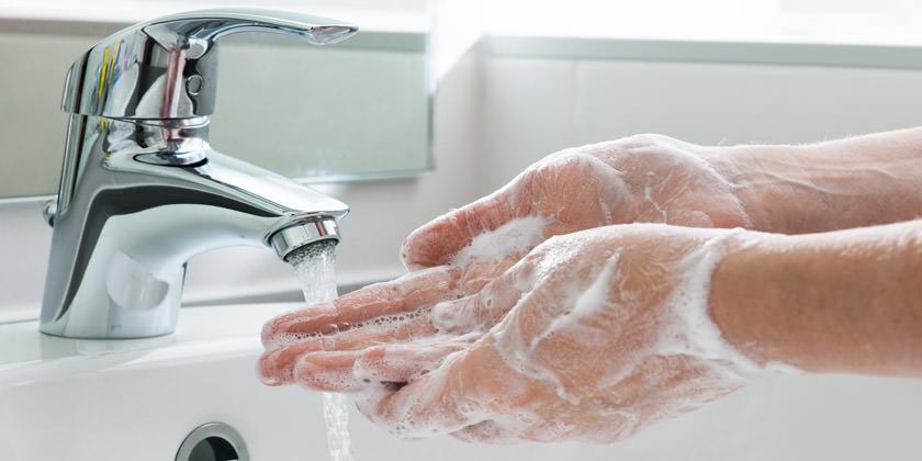 Manos con jabón debajo del grifo