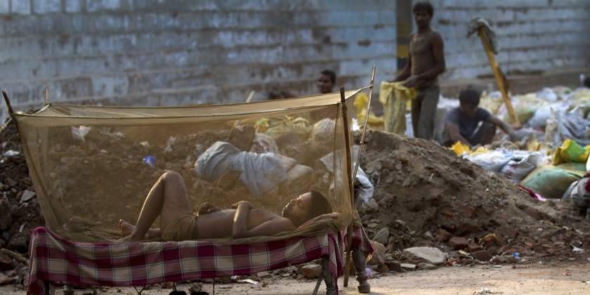 Hombre en una cama con mosquitera en India.