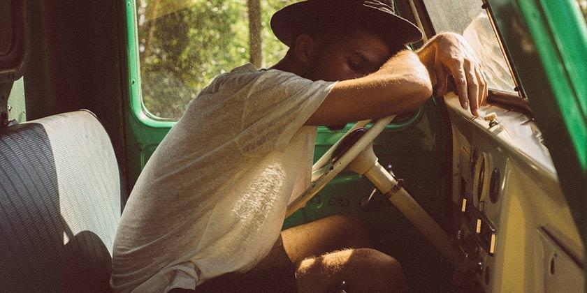 Chico joven durmiendo encima del volante de su vehículo