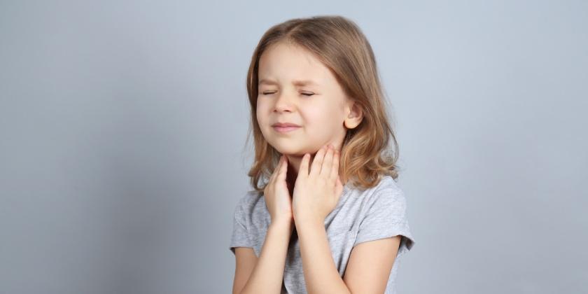 Niña con rigidez en la nuca, uno de los síntomas de la meningitis.