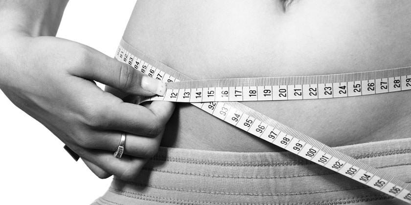 Mujer midiéndose la cintura con un metro