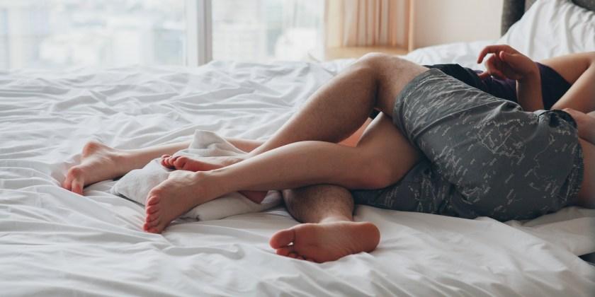 Pareja en la cama manteniendo relaciones sexuales.